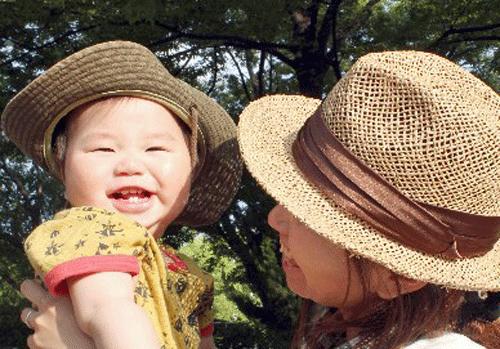 帽子をかぶる赤ちゃんとお母さんの画像