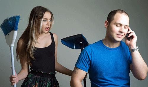 家事をする女性とスマホを触る男性の画像