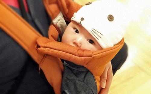 赤ちゃんが茶色の抱っこひもで抱っこされている画像