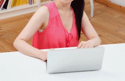 パソコンを操作するピンク色の服を着た女性の画像